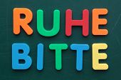 German term for quiet please in colorful letters on a blackboard.