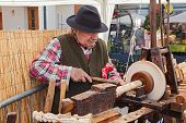 An Artisan Working The Wood With An Antique Lathe