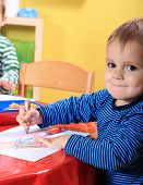 Cute caucasian toddler drawing a picture in kindergarten.