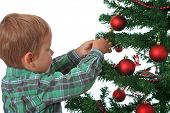 Cute caucasian boy decorating the christmas tree. All on white background.