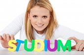 Attractive teenage girl building the german term Studium (eng. study) out of colorful letters. All o