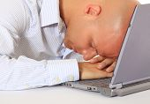 Attractive middle aged man fell asleep on his laptop. All on white background.