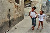 Tanzania, Zanzibar, Stone Town, Two Dark-skinned Girls Playing In Street.