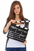 Attractive teenage girl holding clapperboard. All on white background.