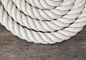 Heavy rope on weathered wooden background.
