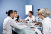 stock photo of business meetings  - Business group having a meeting and they discuss and laughing togetherblank chart for presentation in background - JPG