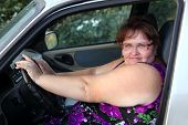 overweight woman sitting behind the wheel of car