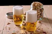 Beer With Peanuts On Old Wood Table