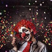 stock photo of comedy  - Insane circus clown with smile holding miniature balloons under falling confetti during a birthday party celebration at a hospital ward - JPG
