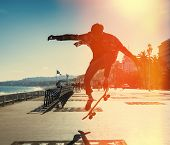stock photo of skateboarding  - Silhouette of Skateboarder jumping in city on background of promenade and sea - JPG