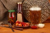 Beer and grilled sausages on wooden table on  sackcloth background