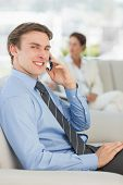 Smiling businessman on the phone sitting on sofa in the office