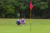 A professional golfer and his caddy reading the green to judge the line of the putt. Series of three