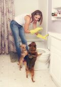 a woman flushing something down the toilet in front of two dogs