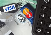 Ratingen, Germany - June 21, 2011: Closeup of credit and debit cards issued by three major brands VISA, American Express and MasterCard with a pocket calculator. Studio shot.
