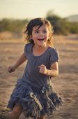 Precious pretty little girl joyfully running outdoors with happy smile on her face.....