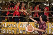 SARAWAK, MALAYSIA: JUNE 1, 2014: A lady passes a drink to Bidayuh tribe children taking part in a st