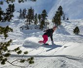 picture of snowboarding  - Young woman snowboarder in motion on snowboard in mountains - JPG