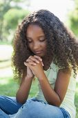 Young girl praying in the park on a sunny day