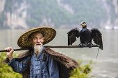 Cormorant fisherman and his bird on the Li River in Yangshuo, Guangxi, China.