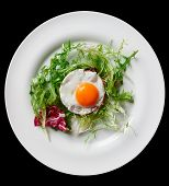 Beef tartar with fried egg and lettuce isolated on black background