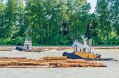 Tug boats work with log boom.