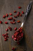 Spice barberry in spoon on wooden background