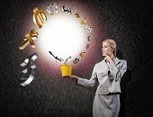 stock photo of bucket  - Young businesswoman holding bucket with currency signs flying out - JPG