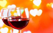 Two Red Wine Glasses On Hearts Decoration Bokeh Lights Background