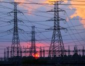 foto of power transmission lines  - beautiful sunset behind electricity plant industry estate use as electrical power background - JPG