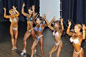 Line Up Of Female Bodybuilding Contestants Showing Their Best