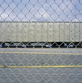 stock photo of railroad yard  - Looking at a train car through a chain link fence - JPG
