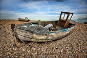 Beautiful view of the sea rocky beach with old old fishing boat, blue cloudy sky, H D R