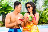 Asian couple drinking fancy cocktails at hotel or club pool