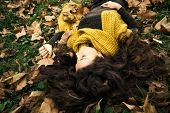 beautiful woman with eyes closed  lie in grass and autumn leaves wearing dark green dress and long yellow wool scarf