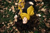smiling beautiful woman  lie in grass and autumn leaves wearing dark green dress and long yellow wool scarf
