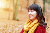 Young pretty woman in red sweater and yellow scarf smiling. Autumn, fall park, forest