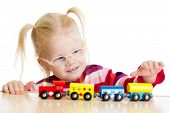 Kid in eyeglases playing toy train isolated on white