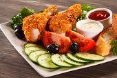 Fried chicken drumsticks and vegetables