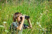 stock photo of boy scout  - Boy hiding in grass looking through binoculars outdoor - JPG