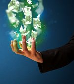 Businessman holding glowing paper moneys in his hand