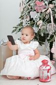 Little girl with the mobile phone sits near a Christmas fir-tree