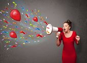 Young girl having fun, shouting into megaphone with balloons and confetti