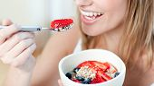 Close-up Of A Woman Eating Muesli With Fruits