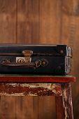 Nostalgic old vintage suitcase on old stool  with textured wood background
