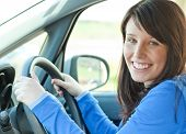stock photo of driving school  - Young and cheerful Woman Driving her car - JPG