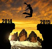Girl jumps to the New Year 2015 in the background Tre cime di Lavaredo, Dolomite Alps, Italy