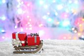 Wooden toy sledge with Christmas gifts  on shiny background
