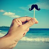 a man hand holding a fake moustache in a stick in his hand on the beach, with a filter effect