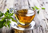 Transparent cup of green tea on wooden background